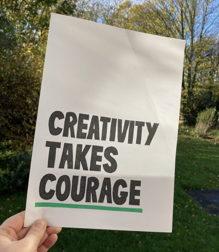 a print saying Creativity takes Courage